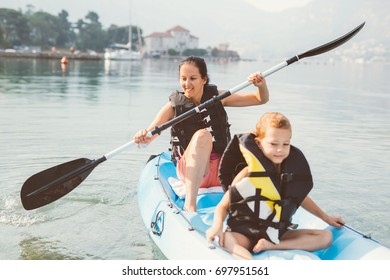Mother and son kayaking at the sea