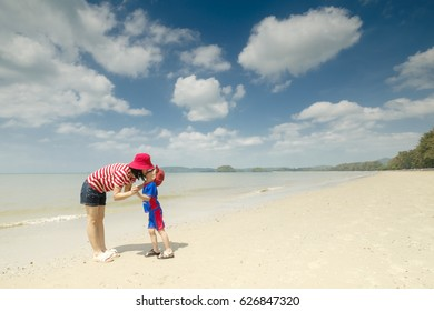 A mother and son kissing on beach outdoors Sea and Blue sky in happy day