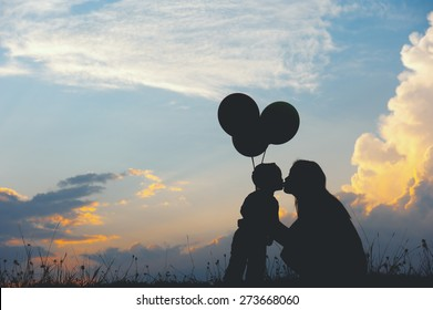 A mother and son kissing outdoors at sunset silhouette