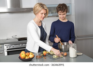 Mother and Son in the kitchen. A beautiful woman in the kitchen with her teenage son.