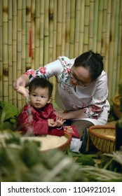 Mother and son is learning about banh chung in Tet holyday.