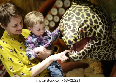 Mother with son looking at moray in zoo