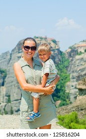 Mother and son looking at the town of Kalambaka bird's eye view. Vertical view. Meteora, Greece.
