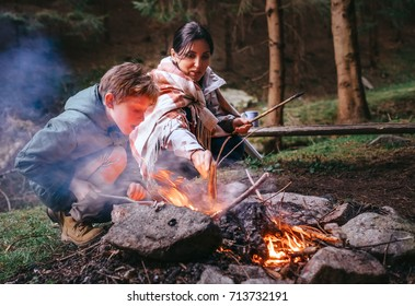 Mother with son make campfire