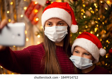 Mother and son make selfie near the fir-tree, both of them in christmas hats and medical masks. Winter holidays celebration during quarantine.