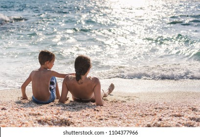 Mother and son making fun on sea sunny beach. Summer vacation holiday concept.