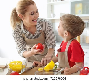 Mother and son making meal together in kitchen. Cooking classes concept