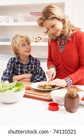 Mother And Son Making Sandwich In Kitchen