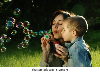 Mother and son making soap bubbles outdoors in the summer park