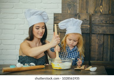 Mother and son mixing flour and eggs in bowl. Woman and child boy in chef hats with spoon. Happy family in kitchen. Homemade baking and cooking. Mothers day concept