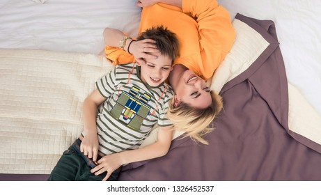 Mother with son on bed, mother and son having fun, mom and her teenager son lying on bed, mother with child relaxing, modern mom with kid at home, top view