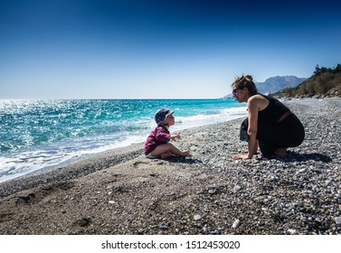 Mother and son on shore with beach in background against clear sky