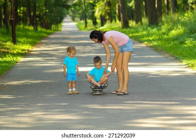 Mother and son on a skateboard. young mother teaches her little boy to ride a skateboard