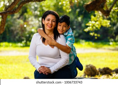 Mother and son outdoor lifestyle portrait in a park setting.