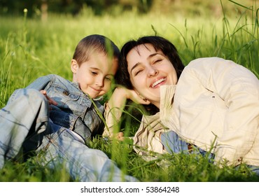 Mother and son outdoors lying on the grass