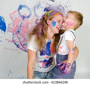 Mutter und Sohn streichen die Wände/Zeichnungen an die Wand. Kind selbst schmutzig in der Farbe und schaut in die Kamera. Kind hat Spaß und Fleck an der Wand. Die Kreativität der Kinder. Kunst für Baby.