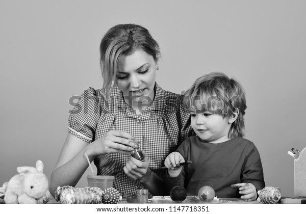 Mother and son painting eggs for Easter. Easter and happy moments concept. Woman and little boy with smiling faces making decorations. Family prepares for holiday on pink background.
