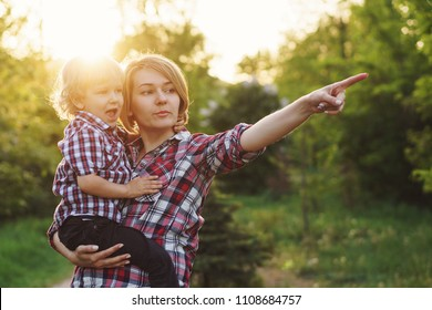 Mother and son in plaid shirts. Woman holds boy in her arms and points to. Family time together.