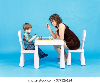 Mother and son play chess. Family and education concept