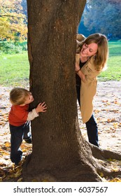 Mother and son play hide-and-seek in autumn park