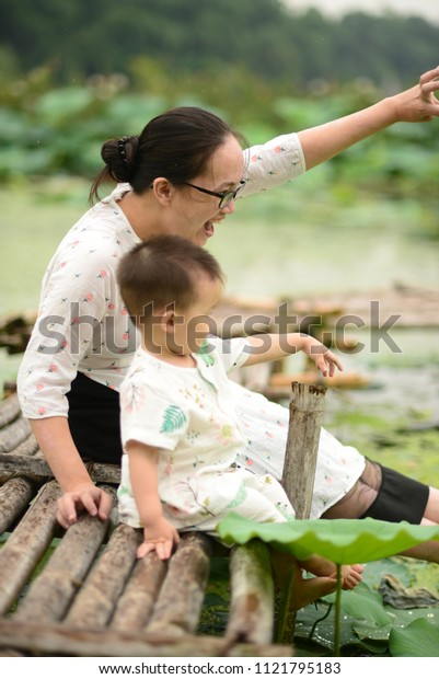 Mother and son play on the lotus pond