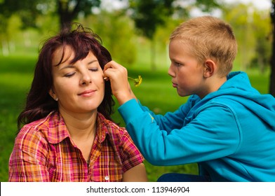 Mother and son play outside on field in the park