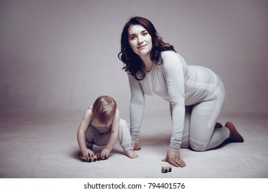 mother and son play, studio shooting, gray clothes, gray background.
