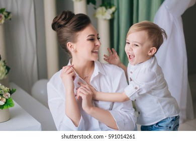Mother and son playing in a brightly lit room. handsome boy with white hair and big eyes. Family in white clothes. Communicate with your child. lovely family