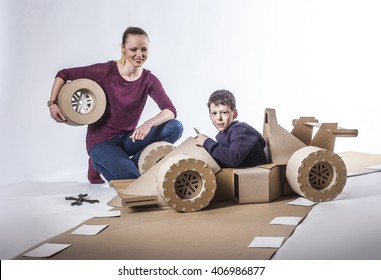 Mother and son playing with a large cardboard racing car. happy family.