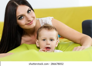 Mother and son playing and looking in camera. Beautiful young smiling woman sitting behind her little boy. Childhood and parenthood concept. Baby-sitter with kid