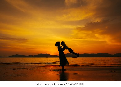 A mother and son playing on the beach and sea outdoors at sunset in happy holiday vacation time with copy space