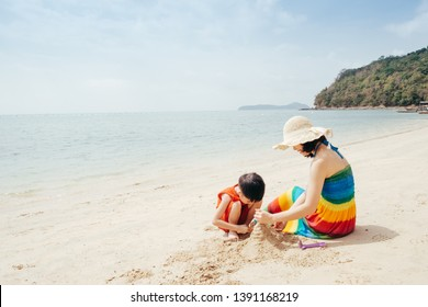 A mother and son playing on the beach and sea outdoors at Blue sky with copy space.Holiday Summer vacation with family concept