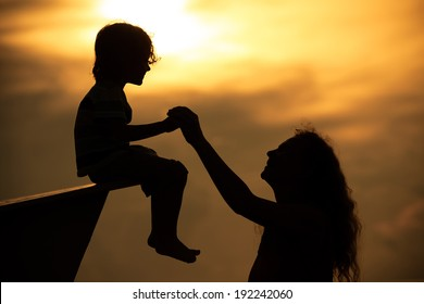 mother and  son playing on the beach in dawn time