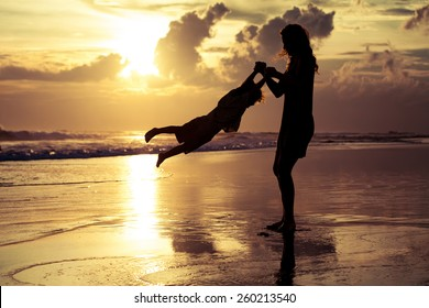 mother and  son playing on the beach at sunset time