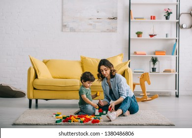 Mother and son playing on carpet in living room