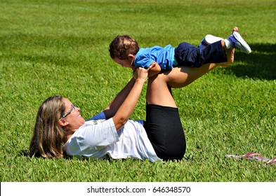 Mother and son playing on grass on sunny day.