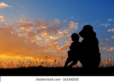 A mother and son playing outdoors at sunset silhouette