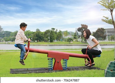 Mother with son playing seesaw in the park.