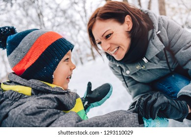 Mother and son playing in the snow and making snowman