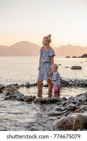 Mother and son is playing in stone pool in sea
