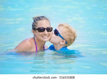 Mother and son playing together in an outdoor swimming pool. Boy kissing his smiling mom in the water. Fun time together