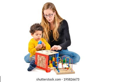 Mother and son are playing together as part of the creative children therapy. A therapist is working with little child. Didactic therapeutic toys for autism.
