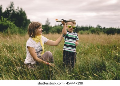 mother and son playing with a toy airplane on a background of an airplane landing