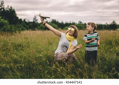 mother and son playing with a toy airplane in a field