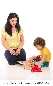 Mother and son playing with toy house in their home