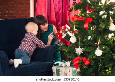 Mother and son preparing for Christmas and the new year: play, read books, prepare gifts and decorate the Christmas tree. Festive  interior with Christmas tree.