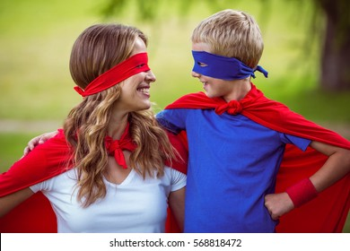 Mother and son pretending to be superhero in park