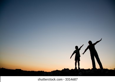Mother and son pretending to fly at sunset.