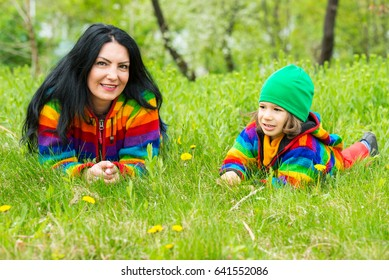 Mother and son in  rainbow hoodies laying on green grass in spring park