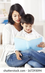 Mother and son reading book in living room